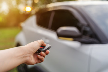 hand using remote key to unlocked car