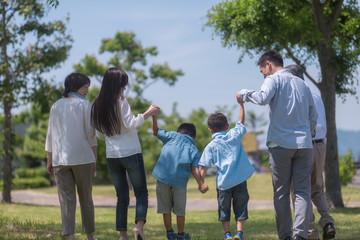手を繋いで公園を歩く三世代家族の後ろ姿