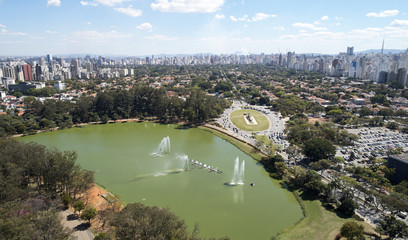Aerial view of Ibirapuera park in Sao Paulo city, Monument to the Bandeiras. Prevervetion area with trees and lake of Ibirapuera park. Office buildings and residential district in the background.