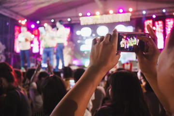Hands with mobile smart phone recording and taking a picture at music concert