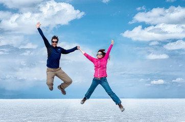 happy couple jumping in Uyuni Salt Flats , Bolivia, South America