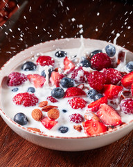 Splash milk from a bowl with a natural diet breakfast with granola, nuts and berries falling on a wooden table.