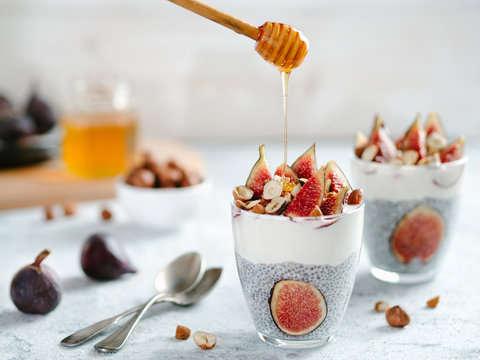 Healthy chia pudding with yogurt, figs and nuts in glass. Ideas and recipes for healthy breakfast, snack or dessert. Honey drips into glass with chia seeds pudding. Copy space for text.