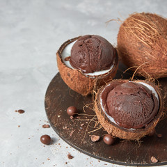 Tasty fresh brown ice cream in a coconut peel with chocolate balls on a round board on a gray.