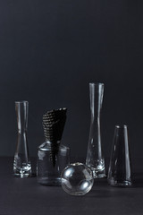 Black waffle cone for ice cream in a glass jar with several glass vases on a black background.