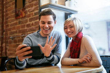 Couple Using On Phone In Cafe For Video Calling Or Taking Photos