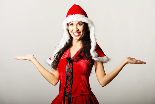 Portrait of woman with open hands gesture wearing santa clothes