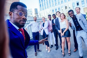 successful and beautiful American afro man in a business suit in a white shirt looking into the phone and takes photos selfie standing company of people on the street . group of nine businesspeople