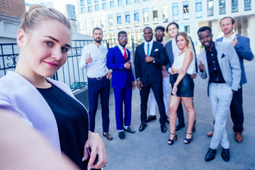 successful group of nine multinational businesspeople in a business suit looking into the phone and takes photos selfie standing company of people on the street .