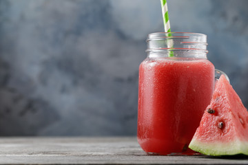 Smoothies cooked from a watermelon in a transparent jar on a wooden table with space for text