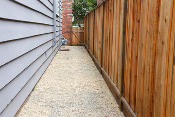 Long narrow side yard, new wood fence on the right with house on the left, home paint chipping and peeling. Meter by brick chimney exterior, fence to front yard with trees