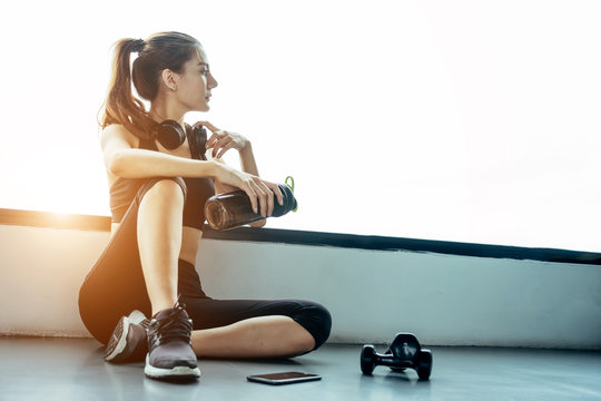 Asian woman exercising in the gym, Young woman workout in fitness for her healthy and office girl lifestyle. She using smart phone to check an email or listening music.