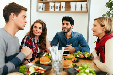 People Having Dinner Together At Table In Cafe