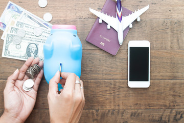 Woman hands saving money in piggy bank with smart phone and passport on table. Creative flat lay of travel concept
