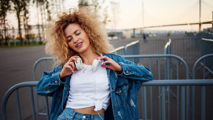 Beautiful and cheerful young woman with lush hair, outdoors. Charming curly hair in a denim jacket.