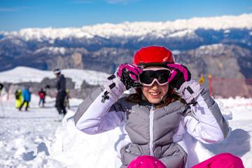 happy little girl arranges ski goggles