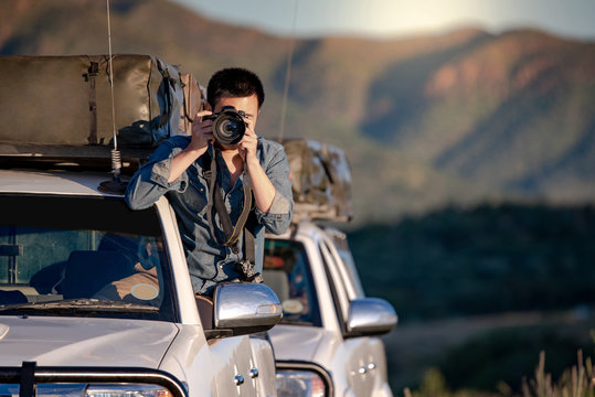 Young Asian male traveler and photographer sitting on the car window taking photo on road trip in Namibia, Africa. Travel photography concept