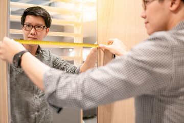 Young Asian man using tape measure for measuring mirror on modern wooden cabinet in walk-in closet showroom. Shopping furniture for home improvement. Interior design concept
