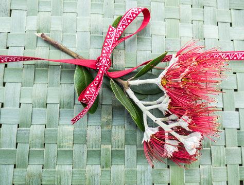 New Zealand Christmas Tree or Pohutukawa flower on woven green flax kete background with ribbon - kiwiana xmas theme