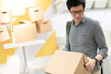 Young Asian man carrying cardboard box choosing what to buy. Warehouse shopping concept