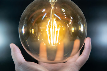 Male hand holding illuminated electric light bulb. Energy saving for future. Concept of inspiration, innovation and idea.
