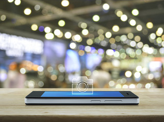 Camera flat icon on modern smart mobile phone screen on wooden table over blur light and shadow of mall, Business camera online shopping and service concept