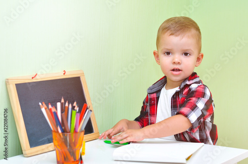 ad0889000 Two year old baby boy in red checkered shirt sitting at table with an album  and colored pencils