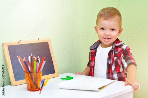 966f9254d Two year old baby boy in red checkered shirt sitting at table with an album  and colored pencils and smiling