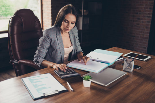 Successful woman in a gray checkered jacket checks documents on