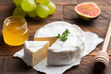 Brie or camembert cheese with figs, grapes and honey on wood