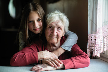 Elderly woman with her little granddaughter.