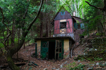 Mystic old abandoned hunter's house in the forest between trees in the dark
