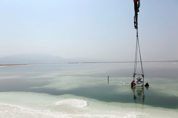 Israeli artist Sigalit Landau (R) stands next to a metal frame containing her artwork, a ballerina's tutu covered in salt crystal formations, as it is removed from the hyper-saline waters of the southern Dead Sea, Israel