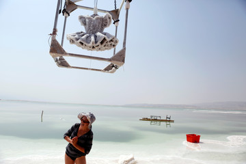 Israeli artist Sigalit Landau laughs as a metal frame containing her artwork, a ballerina's tutu covered in salt crystal formations, is removed from the hyper-saline waters of the southern Dead Sea, Israel