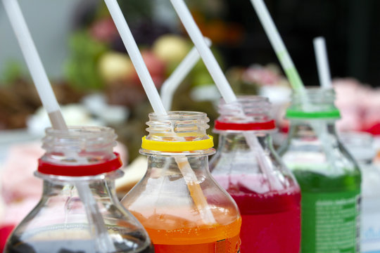 Colorful of carbonated soft drink pop soda bottles with plastic straw. Plastic bottles of assorted carbonated in variety of colors.