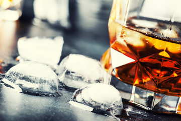 Bourbon with ice in glass on gray bar counter, selective focus