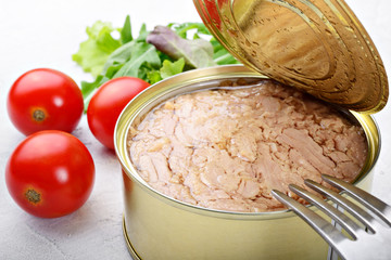 Canned tuna in olive oil with tomatoes and salad on white plaster background