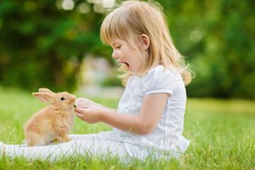 Girl is feeding a cute little rabbit, outdoor, summer day