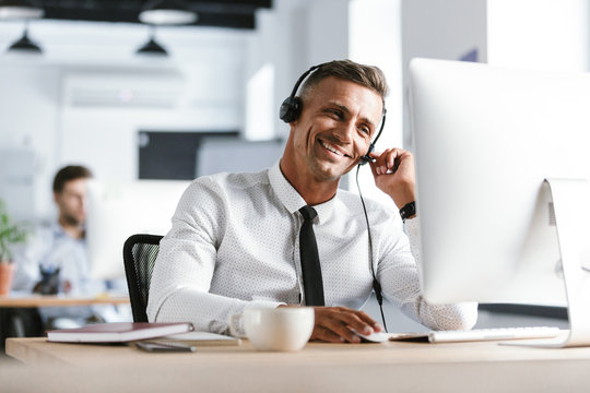 Photo of smiling operator man 30s wearing office clothes and headset, sitting by computer in call center