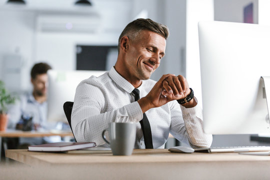 Image of adult businessman 30s wearing white shirt and tie sitting at desk in office by computer, and looking at wrist watch