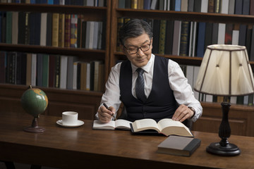 Senior businessman reading book in study