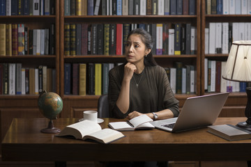Elegant mature woman thinking in study