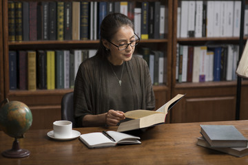 Elegant mature woman reading book in study