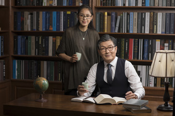 Cheerful mature couple reading book and drinking tea in study