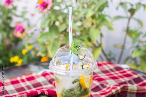 A plastic glass with a tube with mojito with mint and lemon