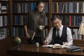 Mature couple reading books in study