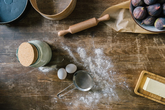 top view of messy wooden table with spilled flour and baking ingredients