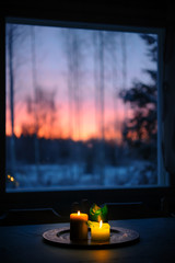 Candles on the table. Winter landscape seen through the window.