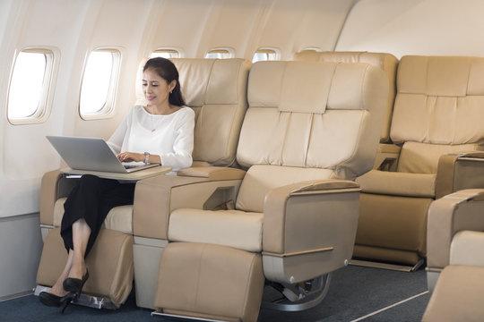 Elegant mature woman using laptop on airplane