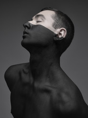 Young man covered in black paint